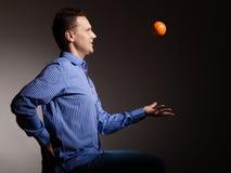 Dieta e nutrição saudável Laranja de jogo do homem Imagens de Stock