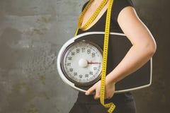 Dieta e peso - giovane donna con una scala immagini stock