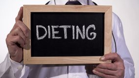 Dieta escrita no quadro-negro nas mãos do doutor, recomendações do nutricionista imagens de stock royalty free