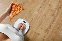 Dieta, fast food Kobieta Na Szalkowej mienie pizzy słucha Fotografia Stock