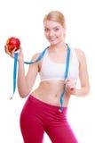 Dieta La muchacha apta de la mujer de la aptitud con la cinta de la medida y la manzana dan fruto Foto de archivo