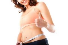 Dieta - la mujer joven está midiendo su cintura Foto de archivo