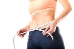 Dieta - la mujer joven está midiendo su cintura Foto de archivo libre de regalías