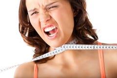 Dieta - la mujer joven se está estrangulando con la cinta Foto de archivo libre de regalías