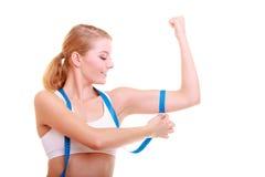 Dieta. Menina apta da mulher da aptidão com medida de medição de fita seu bíceps Fotografia de Stock