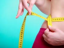Dieta. Muchacha apta de la mujer de la aptitud con la cinta métrica de la medida su cintura Fotos de archivo