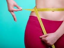 Dieta Muchacha apta de la mujer de la aptitud con la cinta métrica de la medida su cintura Imágenes de archivo libres de regalías