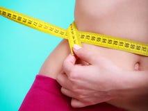 Dieta Muchacha apta de la mujer de la aptitud con la cinta métrica de la medida su cintura Imagen de archivo libre de regalías