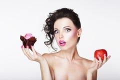 Dieta. Muchacha desconcertante insegura que elige Apple o la torta Imágenes de archivo libres de regalías