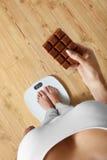 Dieta Mujer en la balanza, chocolate Comida malsana peso Foto de archivo