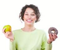 Dieta. Mulher que escolhe entre a fruta e a filhós Fotos de Stock