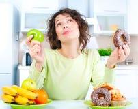Dieta. Mulher que escolhe entre frutas e doces Fotos de Stock
