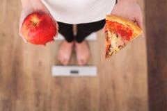 Dieta Peso corporal de medição da mulher na escala de peso que guarda a pizza Os doces são comida lixo insalubre Fazendo dieta, c imagem de stock