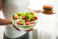 Dieta Peso corporal de medição da mulher no hamburguer e no Salat da terra arrendada da escala de peso Os doces são comida lixo i foto de stock royalty free
