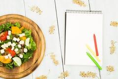 Dieta plan - sałatka świezi warzywa i pusty notatnik dalej obraz stock