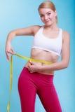 Dieta. Ragazza adatta della donna di forma fisica con la misurazione di nastro di misura la sua vita fotografia stock