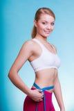Dieta Ragazza adatta della donna di forma fisica con la misurazione di nastro di misura la sua vita fotografie stock libere da diritti