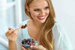 Dieta sana Mujer que come el cereal, bayas por mañana Nutrición foto de archivo