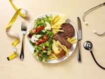 Dieta sana y malsana en una placa Fotografía de archivo