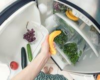 Dieta saudável: Uma mão que agarra uma banana do refrigerador aberto completamente dos verdes Fotografia de Stock