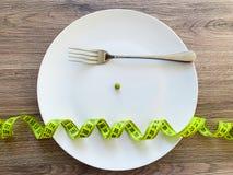 Dieta Sofrimento da anorexia Ervilha colhida da imagem na placa branca, com forquilha e medição fotos de stock