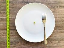 Dieta Sofrimento da anorexia Ervilha colhida da imagem na placa branca, com forquilha e medição foto de stock