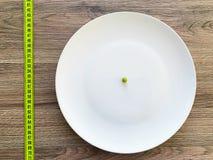 Dieta Sofrimento da anorexia Ervilha colhida da imagem na placa branca foto de stock royalty free