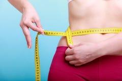 dieta Sprawności fizycznej kobiety napadu dziewczyna z miarą taśmy mierzy jej talię Fotografia Royalty Free