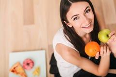 Dieta Uma jovem mulher olha sua figura e comer o fruto fresco O conceito de comer saudável Fotos de Stock