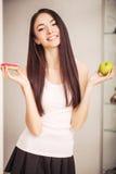 Dieta Uma jovem mulher que guarda uma pizza nas escalas e faz uma escolha entre uma maçã e uma filhós O conceito de comer saudáve Foto de Stock