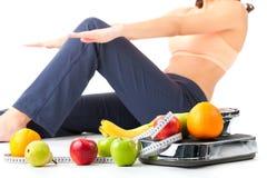 Dieta y deporte - la mujer joven está haciendo sentar-UPS Fotos de archivo libres de regalías