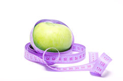 Dietary apple. Large green apple and centimetre ribbon royalty free stock photo