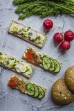 Dietary bread with quail egg and radish, as well as with caviar and cucumbers. Vegetarian sandwiches. Light background. Close-up.  royalty free stock photos