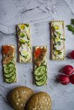 Dietary bread with quail egg and radish, as well as with caviar and cucumbers. Vegetarian sandwiches. Light background. Close-up.  stock photography