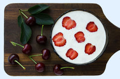 Dietary breakfast - yogurt decorated with strawberries and cherries on wooden board.Rustic style. Dark Tones. A dietary and healthy breakfast - yogurt whipped Stock Image