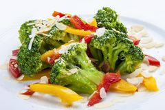 Dietary broccoli with vegetables and peanuts. On a white plate. On white background royalty free stock photo