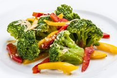 Dietary broccoli with vegetables and peanuts. On a white plate royalty free stock image