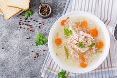 Dietary chicken soup with rice and carrots. Healthy food. Flat lay. Top view Stock Image