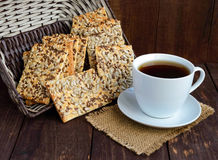 Dietary crunchy cracker with cereals (sunflower seeds, flax and sesame) and a cup of tea on a dark Royalty Free Stock Photos