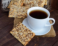 Dietary crunchy cracker with cereals (sunflower seeds, flax and sesame) and a cup of tea on a dark Stock Photos