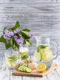 Dietary detox drink with lemon juice, ginger, cucumber and mint leaves in clear water with ice. Close up Stock Photos