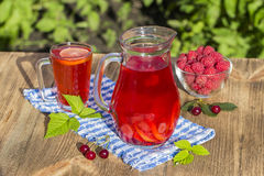 Dietary detox drink with lemon juice, red strawberry, cherry and raspberry in clear water with ice Royalty Free Stock Photography