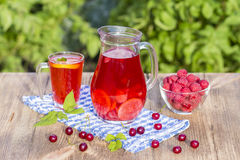 Dietary detox drink with lemon juice, red strawberry, cherry and raspberry in clear water with ice Stock Photography