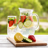 Dietary detox drink with lemon juice, red strawberry, cucumber and mint leaves in clear water Royalty Free Stock Photos