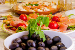 Dietary. Dishes served at the table, with salmon, tomatoes, shrimp, arugula and olives Stock Photo