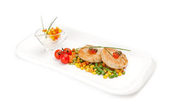 The dietary fish cutlets served with a garnish from corn and asparagus haricot. Stock Photos