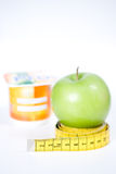 Dietary food concept. Tape measure coiled around apple with yogurt pot in background, dieting concept isolated on white background Stock Images