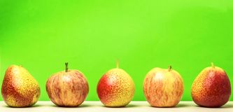 Dietary food. Fresh ripe apples and pears on a green background. Stock Images