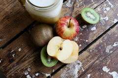 Dietary food. Fruit and milk drink on a wooden background. Kiwi apples on a dark background. Subject of obesity and health royalty free stock photography