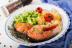 Dietary menu. Baked salmon steak with cauliflower, tomatoes and herbs. Proper nutrition. Healthy lifestyle royalty free stock photos